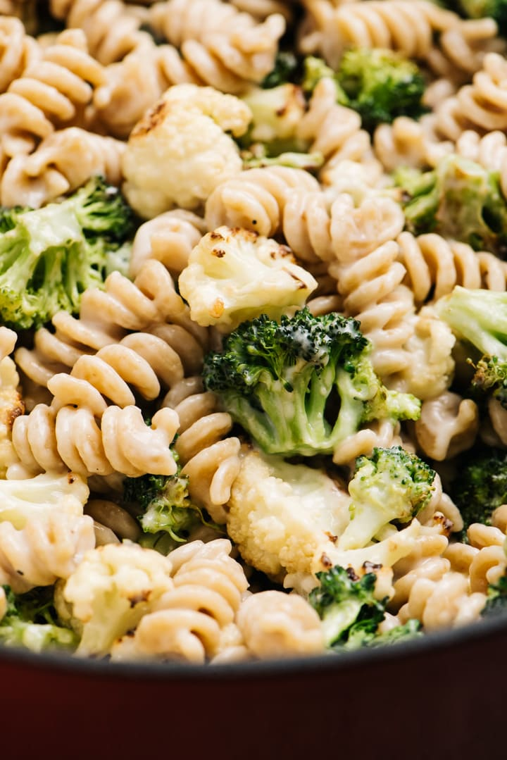 Detail of whole grain pasta tossed with creamy pasta sauce and roasted vegetables in a large pot.