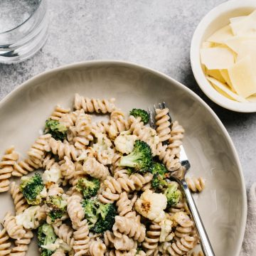 A bowl of whole wheat pasta tossed with creamy pasta sauce and roasted vegetables.