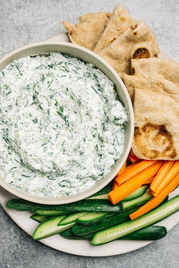 A bowl of healthy greek yogurt spinach dip surrounded by cut vegetables and pita bread.