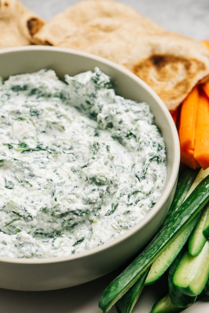 A bowl of greek yogurt spinach dip surrounded with sliced vegetables and pita bread wedges.