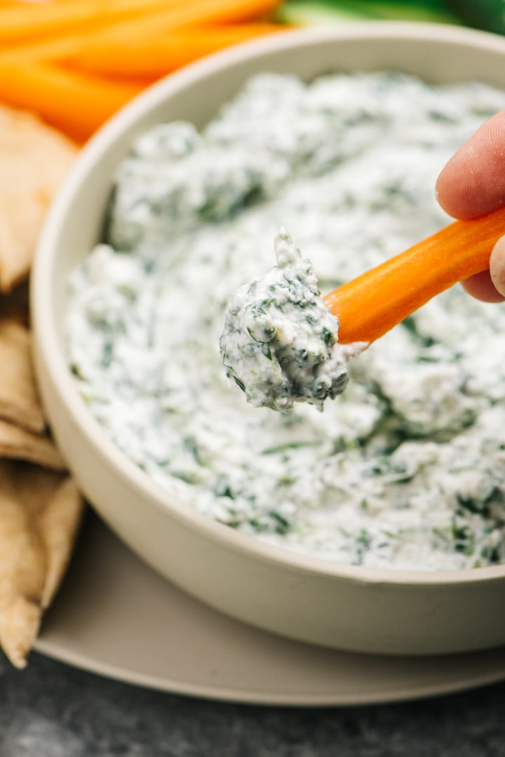 A dollop of healthy spinach dip on a carrot stick.