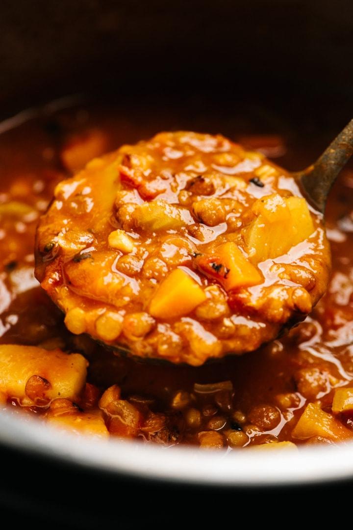 A ladle of vegan lentil soup hovering over an instant pot.