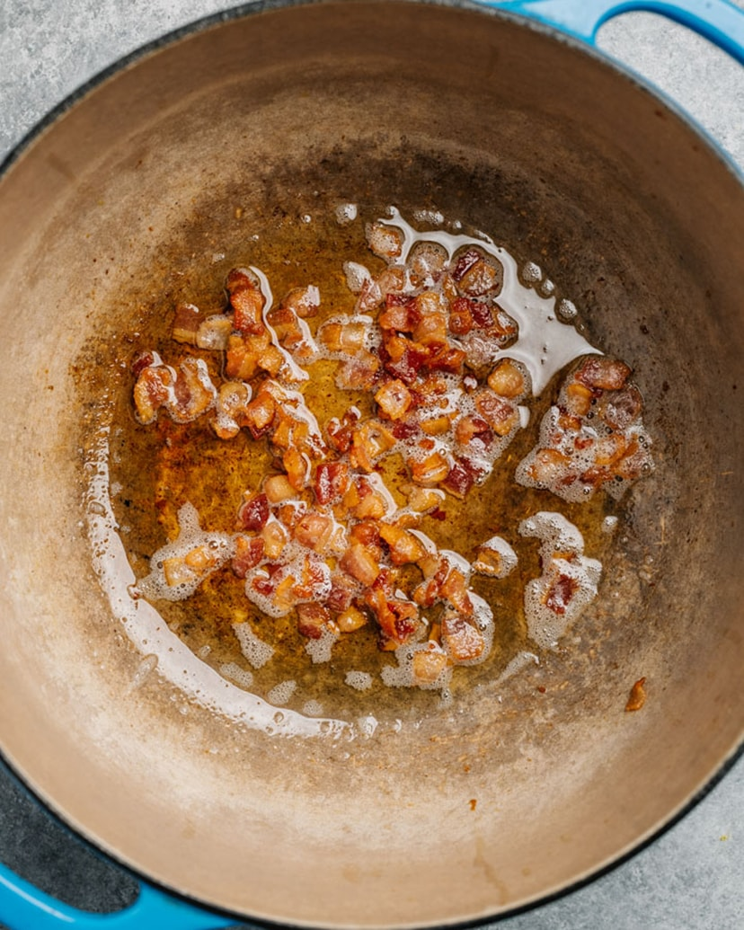 Chopped bacon cooking in a blue soup pot.