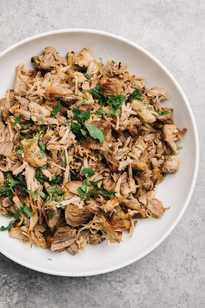 A white serving bowl of carnitas cooked in an instant pot.