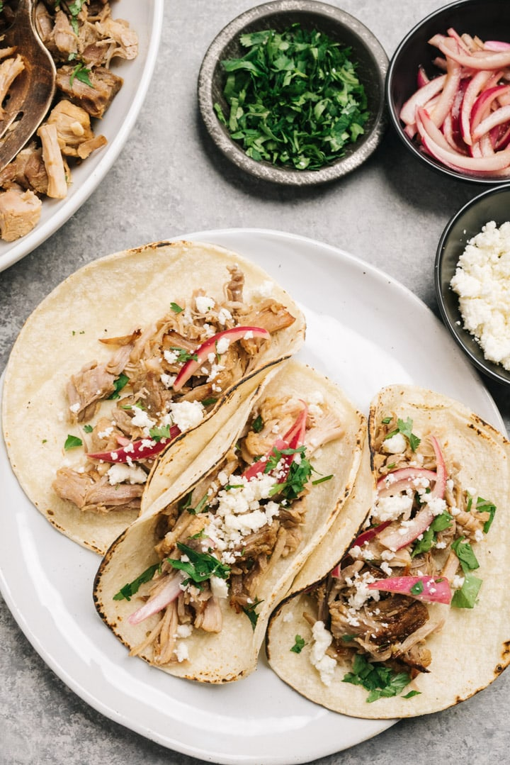 Three tacos stuffed with instant pot carnitas and topped with cilantro, pickled red onion, and cojita cheese.