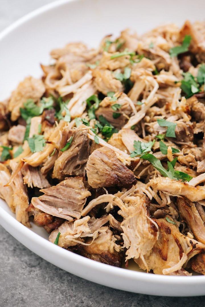 Side view, a bowl of instant pot carnitas garnished with chopped cilantro.