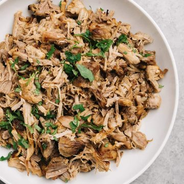 A white serving bowl of instant pot carnitas garnished with chopped cilantro.