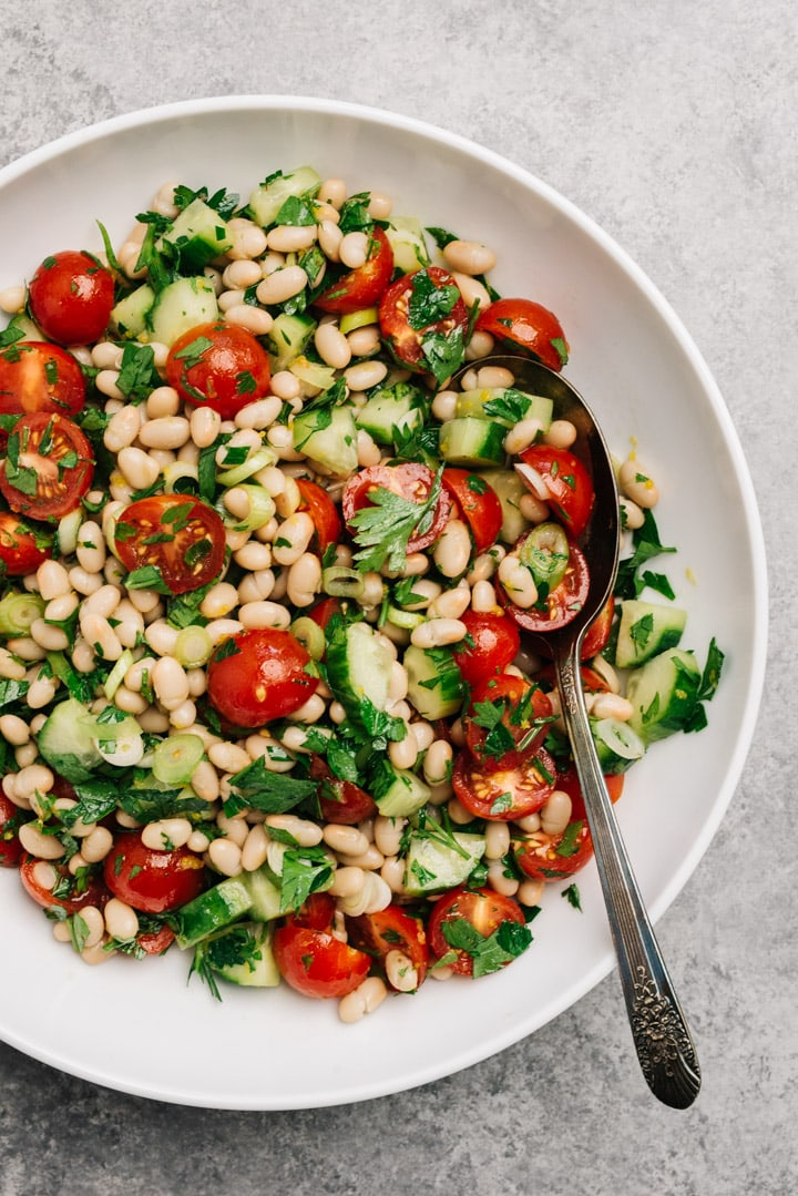 Vegan white bean and tomato salad in a large white serving bowl with a silver serving spoon.