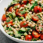 Side view, white bean salad with tomato, cucumber, and parsley in a large serving bowl.