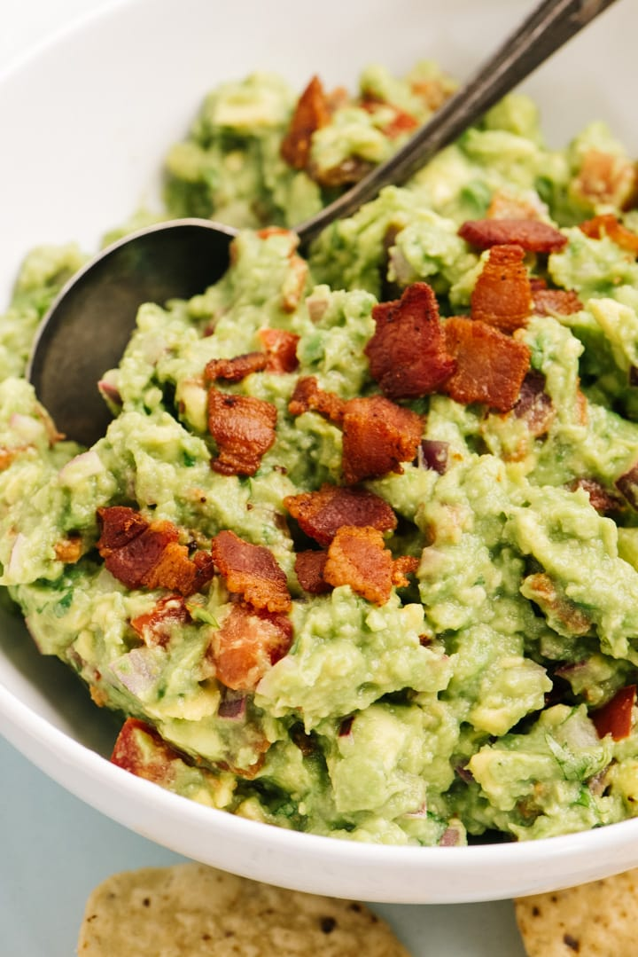 Side view, bacon guacamole in a white bowl with crispy bacon bits on top.