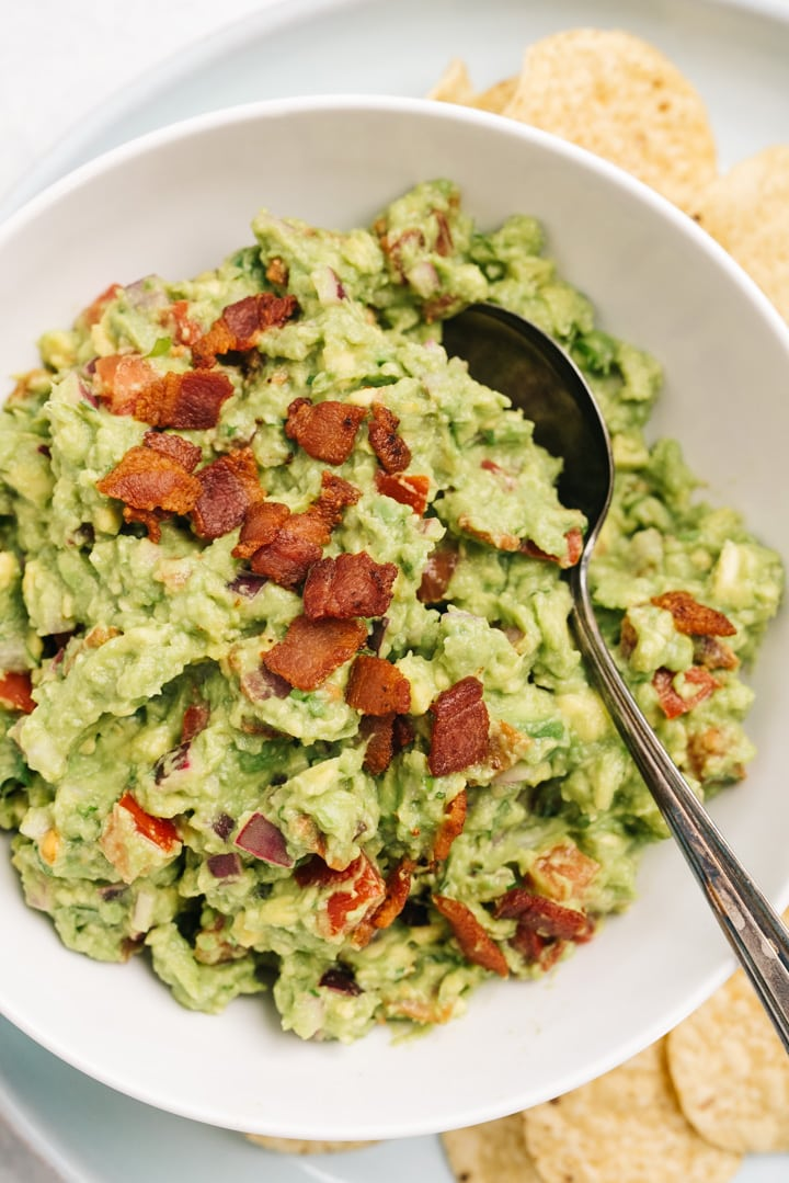 A white serving bowl filled with bacon guacamole topped with bits of crispy bacon pieces.