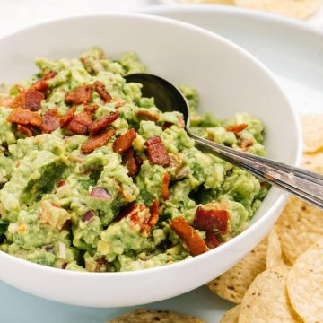 Side view, homemade bacon guacamole in a white bowl surrounded with tortilla chips.