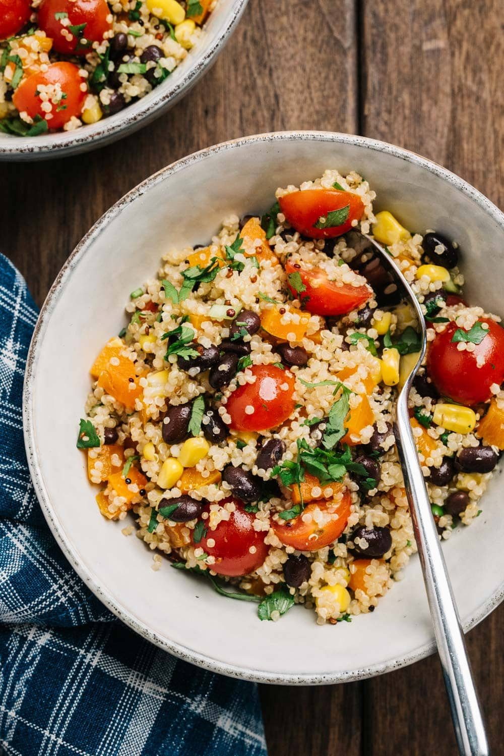 A bowl of black bean quinoa salad with southwestern spices, corn, bell pepper, and tomatoes.