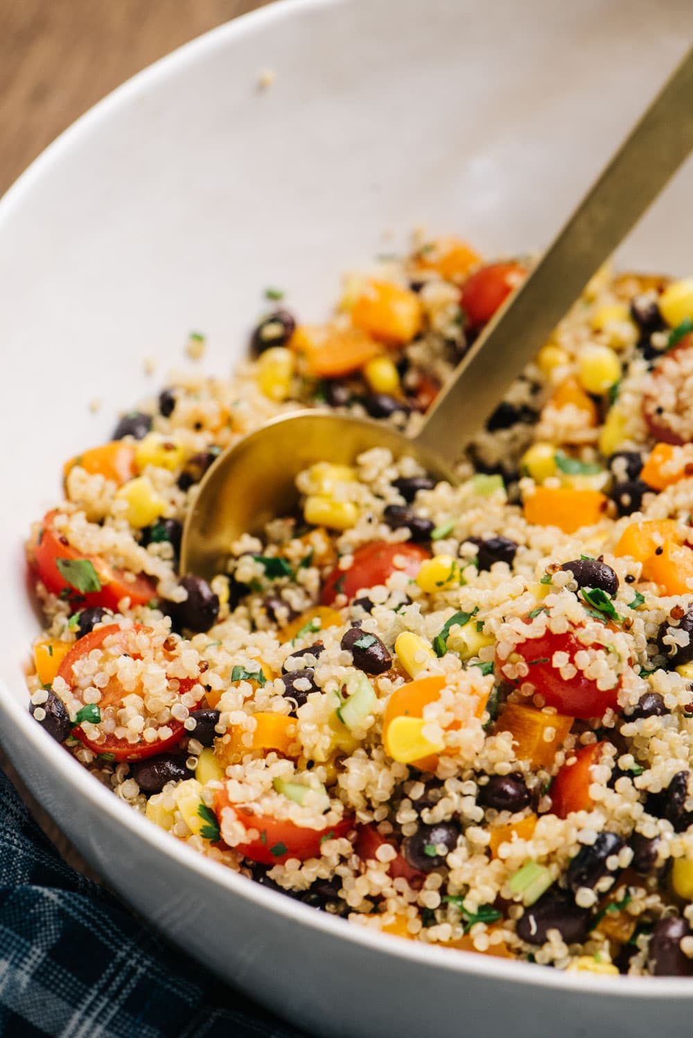 A large serving bowl of southwestern black bean quinoa salad with a gold serving spoon.