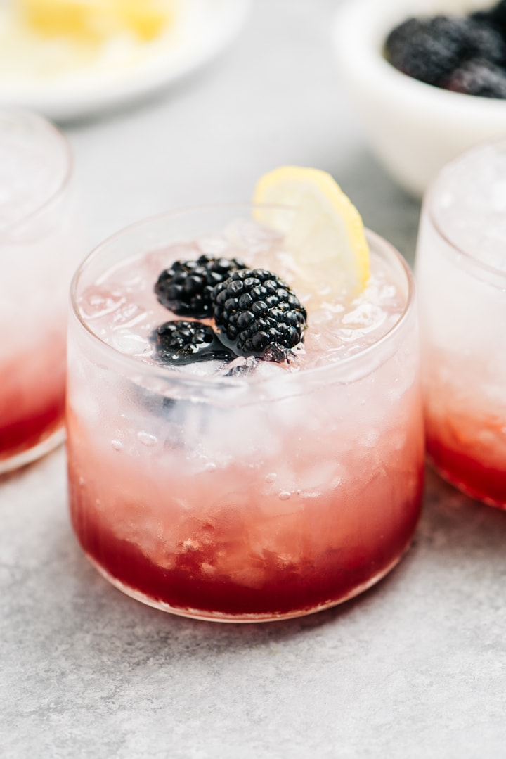 Three gin and blackberry cocktails on a cement surface with small bowls of fresh blackberries and lemon wedges.