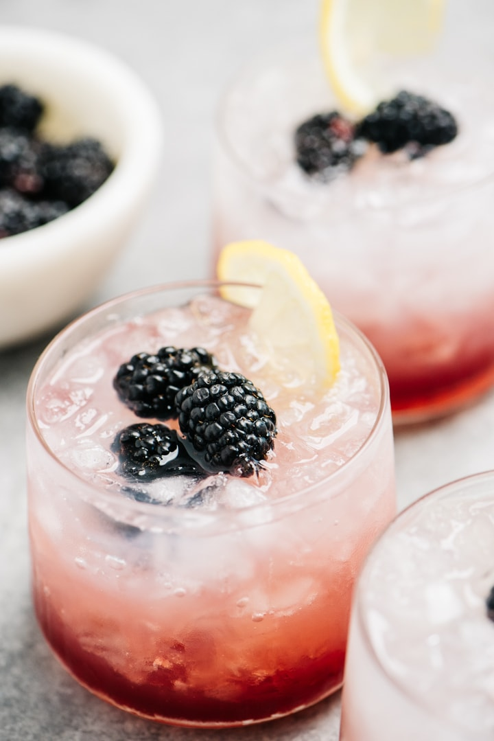 A trio of bramble cocktails with a small bowl of fresh blackberries.