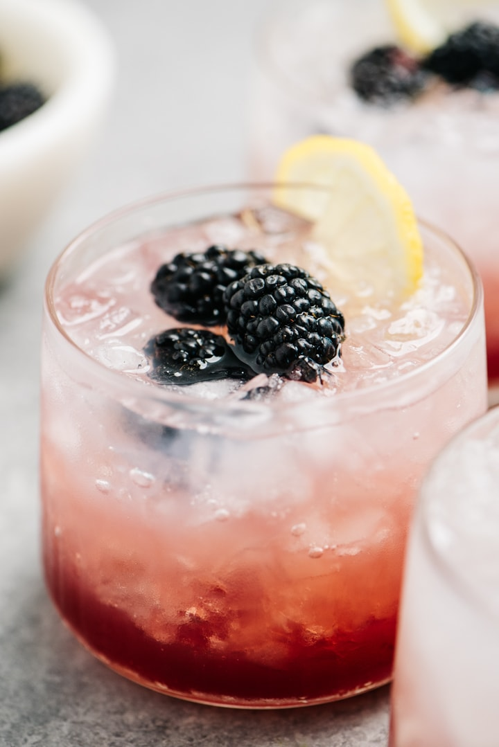 Three bramble cocktails on a cement surface.