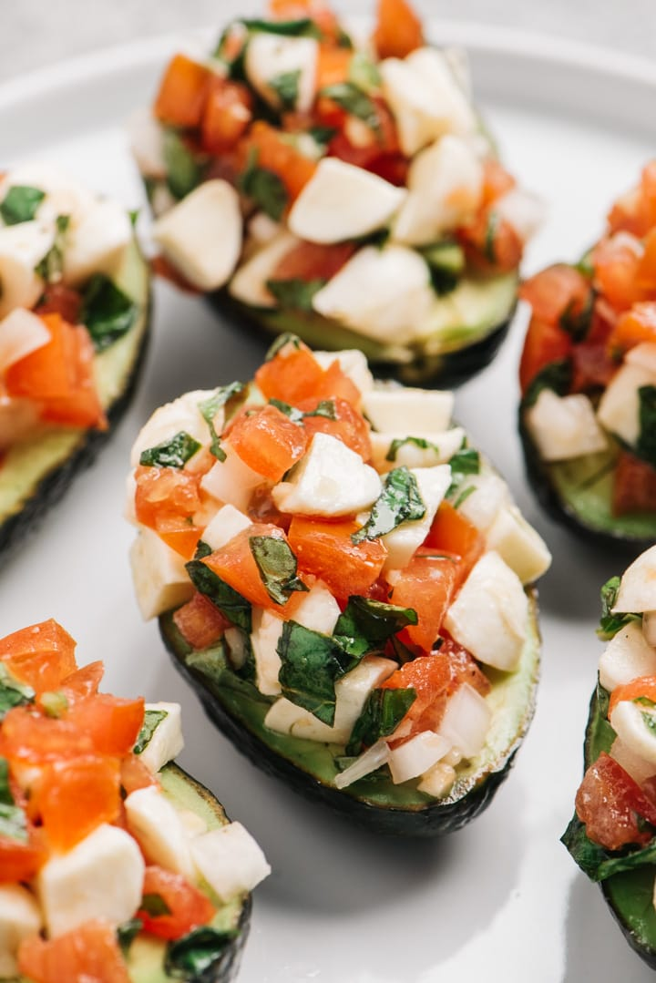 Side view, bruschetta stuffed avocados on a grey plate.
