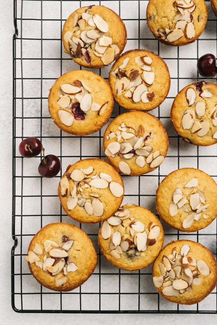 Cherry almond muffins on a wire rack.
