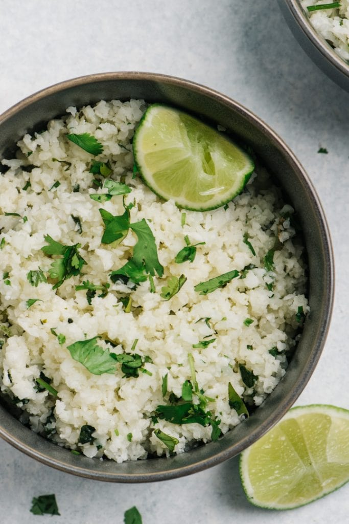 A bowl of cilantro lime cauliflower rice with lime wedges and fresh cilantro.