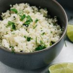 Side view, a bowl of cauliflower rice seasoned with cilantro and lime.