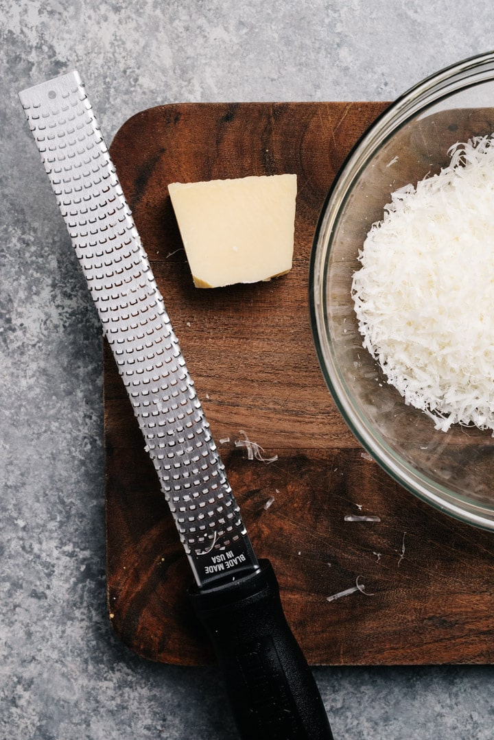 Finely grated parmesan cheese in a small bowl next to a microplane and a chunk of parmesan cheese.