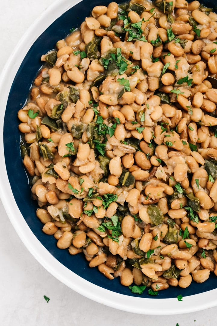 A large serving bowl of pinto beans cooked in an instant pot with poblano peppers and mexican spices.