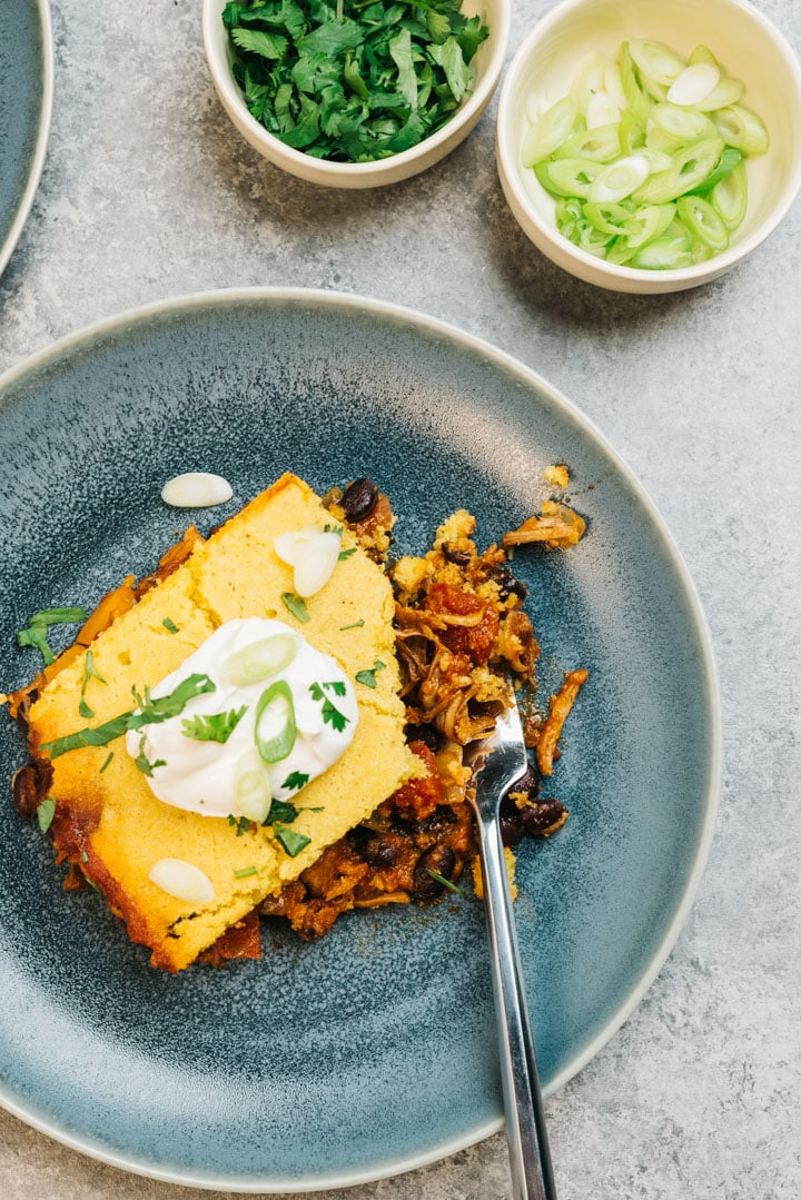 A slice of leftover pulled pork tamale pie with a bite removed on a blue plate, garnished with sour cream, cilantro, and green onions.