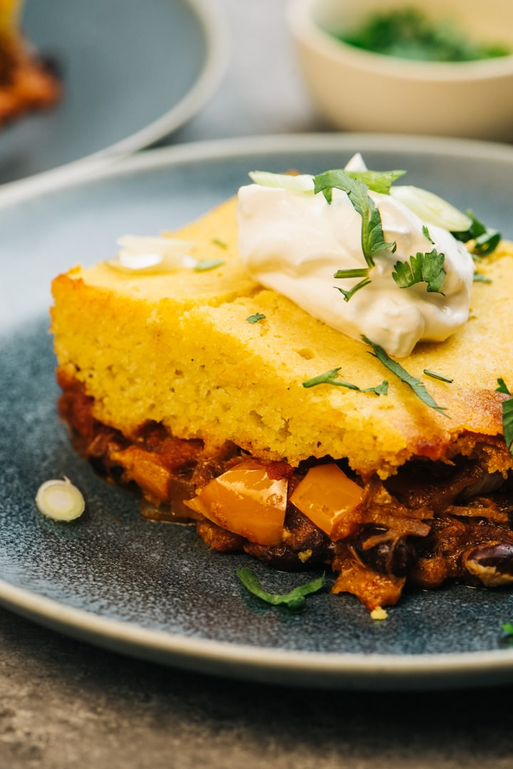 Side view, a slice of pulled pork tamale pie on a blue plate showing the layers of pork and cornbread topping.