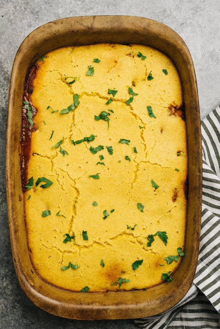 Pulled pork tamale pie in a casserole dish garnished with chopped cilantro.