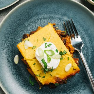 A slice of pulled pork tamale pie on a blue plate topped with sour cream, cilantro, and sliced green onions.