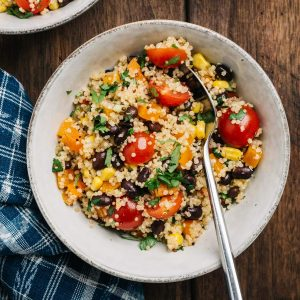 A bowl of black bean quinoa salad on a wood table with a blue patterned linen napkin.