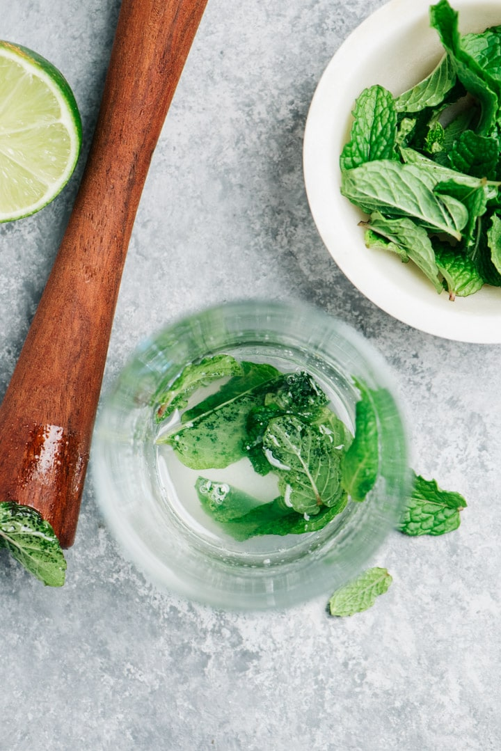 An overhead view into a tall collins glass showing how to properly muddle mint for a mojito cocktail.