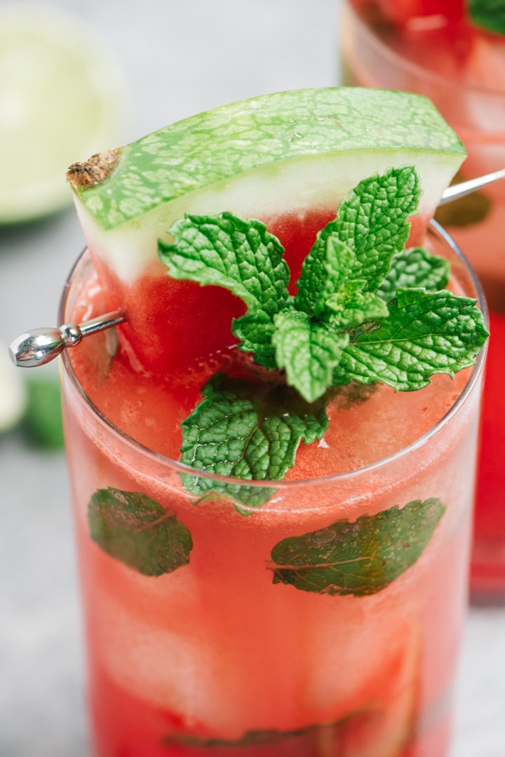 Detail shot of a watermelon mojito cocktail made with mint, lime, and rum.
