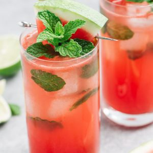 Two mojitos made with watermelon juice on a cement background surrounded by watermelon and lime wedges.