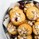A batch of cherry muffins in a bowl lined with a tan linen napkin.