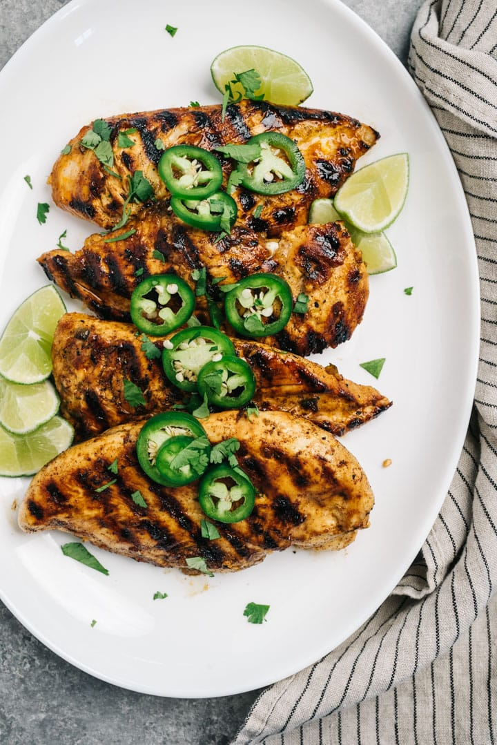 A white platter of grilled chicken marinated in chili lime seasoning.