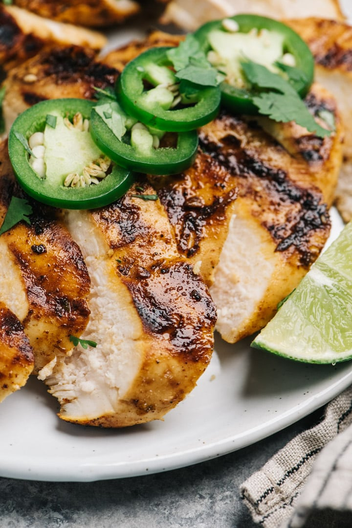 Side view, slices of chili lime chicken topped with thinly sliced jalapenos.