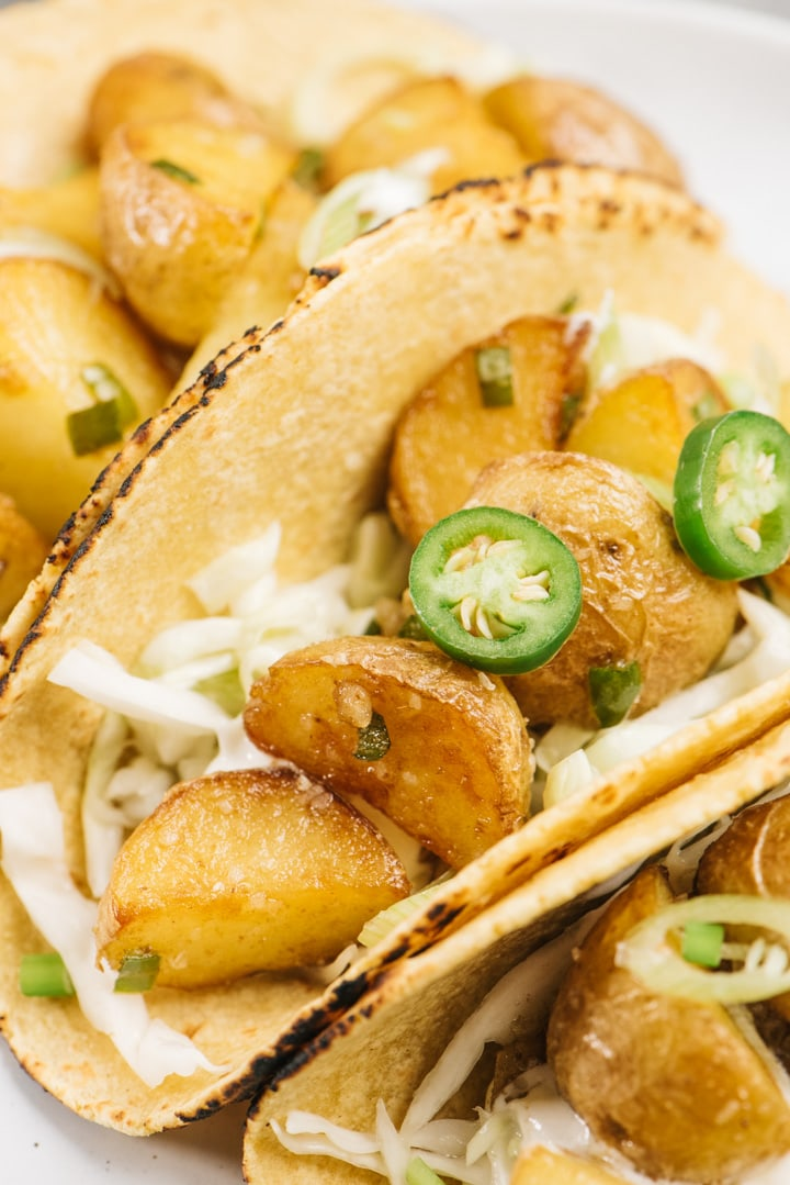 Three vegetarian crispy potato tacos on a white plate served with lime coleslaw, sour cream, and sliced chilies.