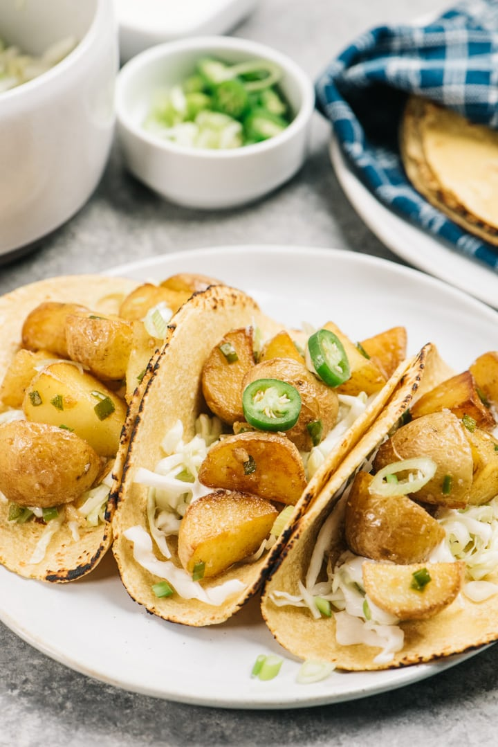 Three vegetarian potato tacos on a white plate topped with sliced chilies, served with lime slaw.