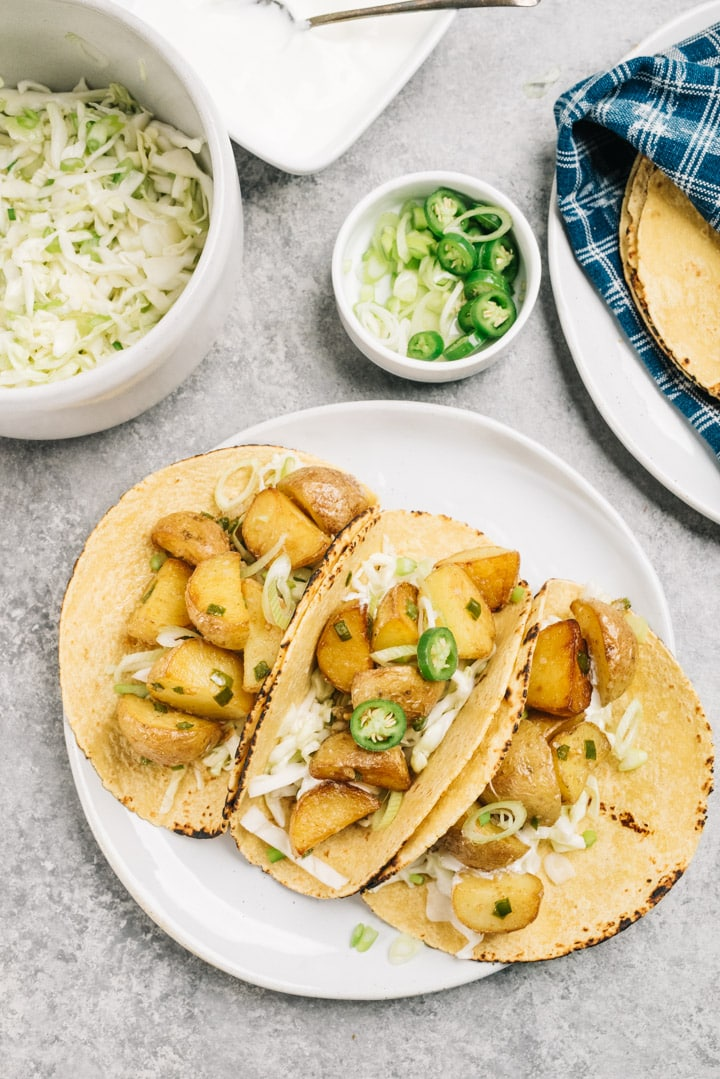 Three spicy potato tacos on a plate surrounded by bowls lime coleslaw, sour cream, sliced chilies, sliced green onions, and a plate of warm tortillas.