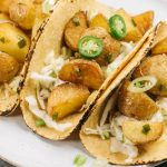 Three spicy potato tacos on a white plate served with lime slaw, sour cream, and sliced chilies.