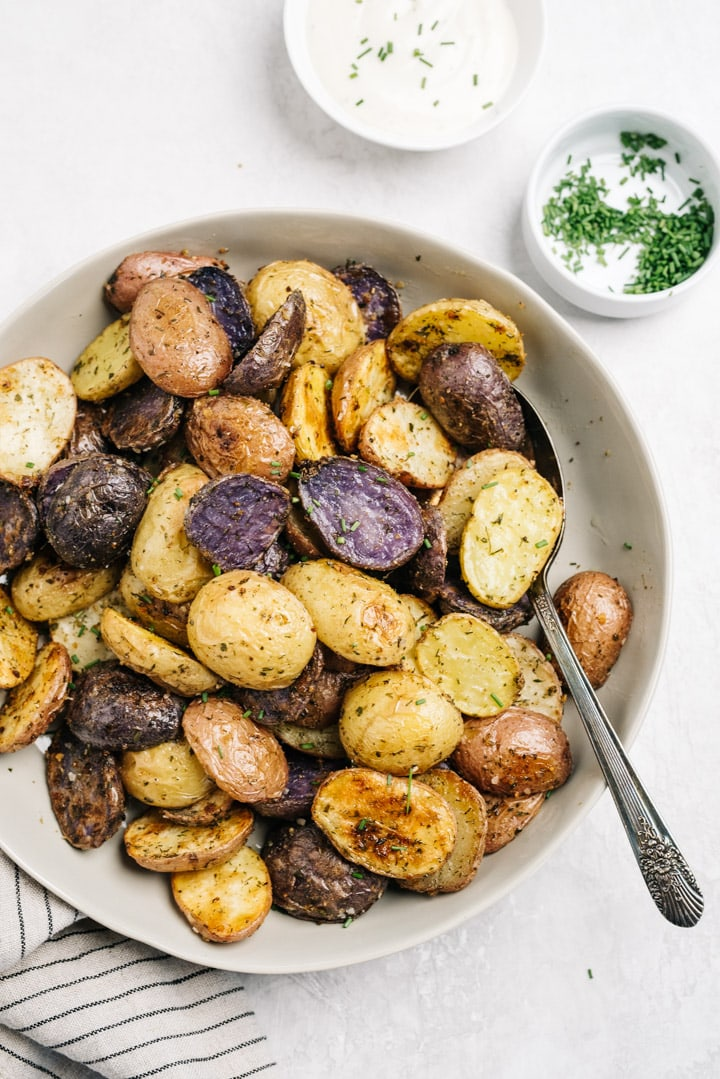 A serving bowl of oven roasted ranch potatoes on a concrete background with small bowls of ranch dressing and minced chives.
