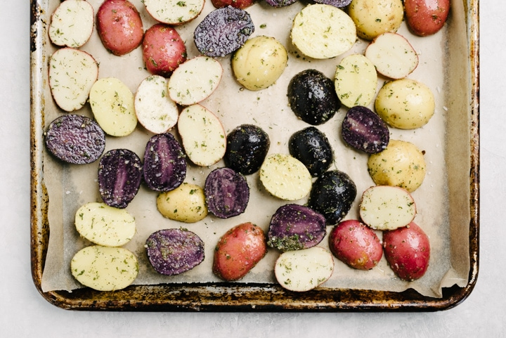 Baby new potatoes seasoned with ranch spread onto a baking sheet lined with parchment paper.