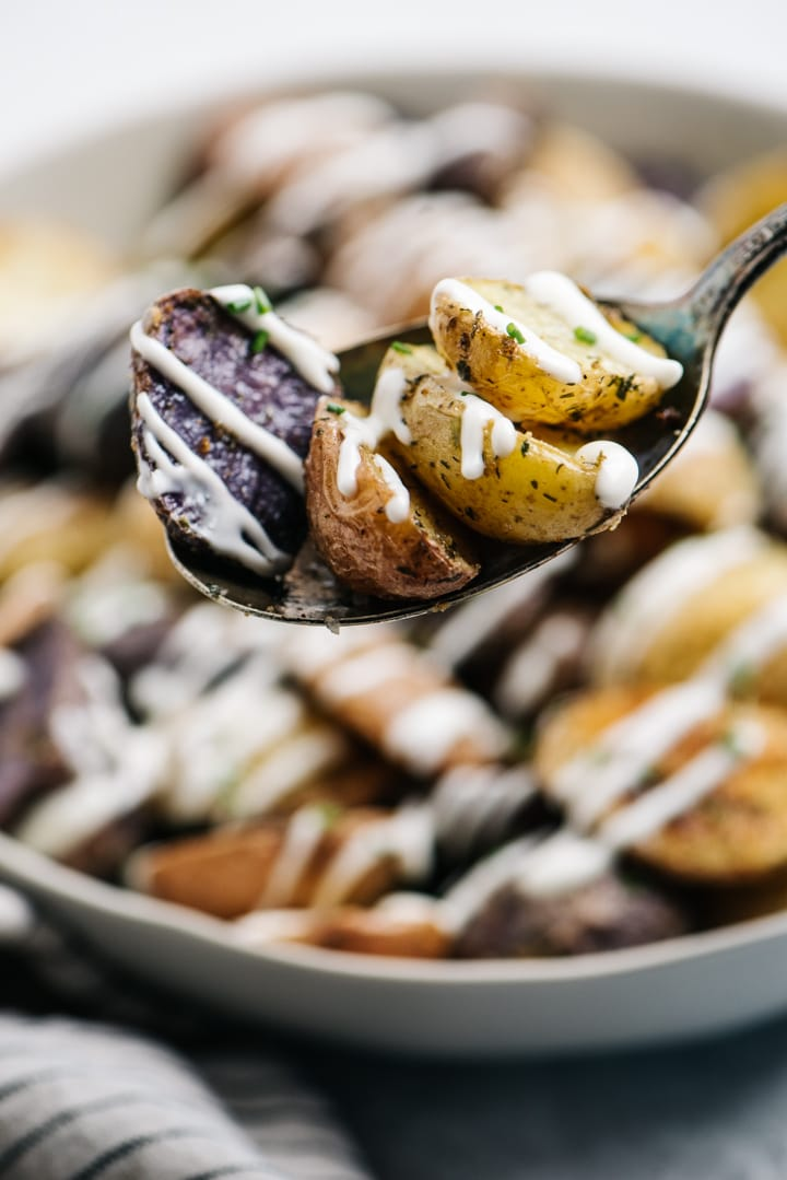 A large serving spoon of roasted ranch potatoes hovering over a serving bowl.