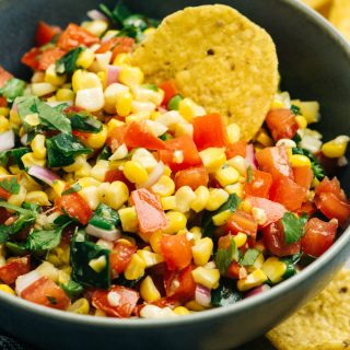 A blue bowl of roasted corn salsa surrounded with tortilla chips.
