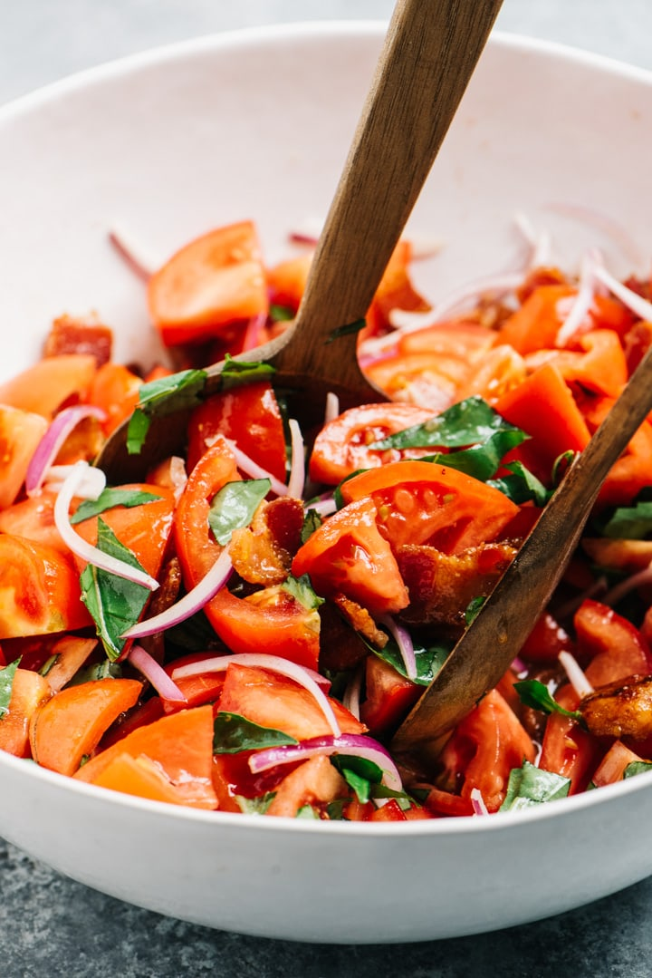 Tomato salad with bacon dressing being tossed in a large white salad bowl with wood tongs.