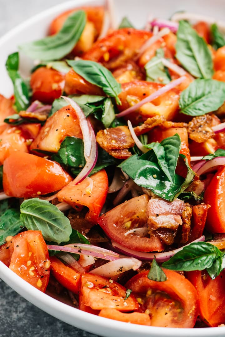 Detail side view of a tomato salad with bacon, red onion, and basil.