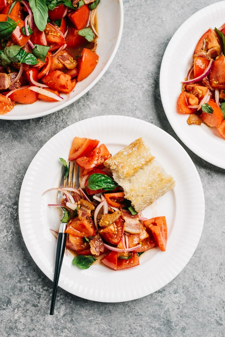 Two plates of tomato salad with bacon dressing served with bread on a cement background.