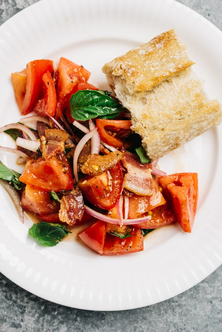 A serving of tomato salad on a white plate with a heel of crusty bread.